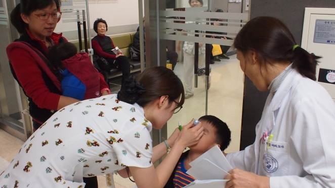 Putting eye drops to dilate Yi Ken's eye